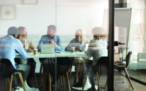 view tthrough a glass wall of a small group of coworkers in a conference room having a meeting