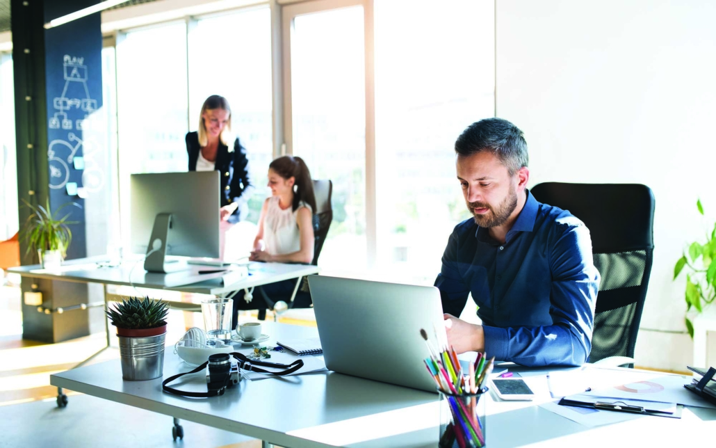 worker sitting at desk with laptop with other coworkers in background at a different desk