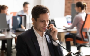 worker using business landline to make phone call